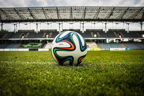 Foto på en fotboll som ligger på en stor fotbollsplan.