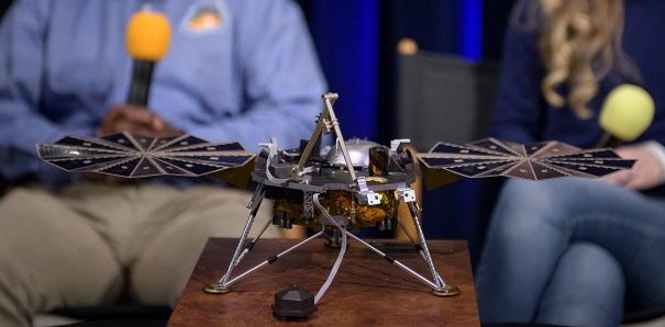 På ett bord står en liten modell av en maskin. Den har tre ben och en metallkropp. På sidorna går det ut två saker som ser lite ut som vingar.