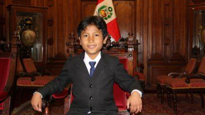 José sitter i en stor trästol. Han har kostym och slips på sig. Han har svart kort hår som är delat i en mittbena och ler mot kameran. I bakgrunden syns Perus flagga.