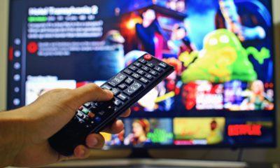 En hand som håller i en fjärrkontroll. I bakgrunden syns en tv-skärm.