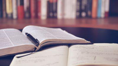 Två böcker ligger uppslagna på ett bord tillsammans med en tjock penna. Den en boken är en anteckingsbok.