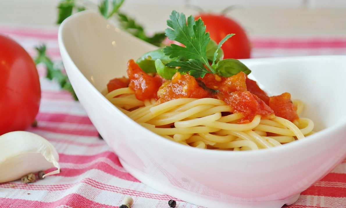 En vit skål med pasta och tomatsås
