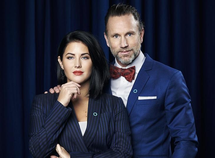 Peter Jihde har blå kavaj och röd slips. Han har lagt sin hand på Mollys axel. Molly har en blårandig kostym och håller ena handen lyft till hakan.