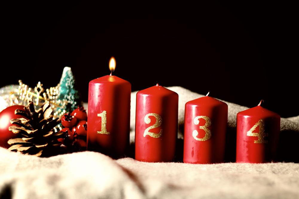 Fyra tjocka ljus som är olika höga, det till vänster är högst och det till höger är kortast. Bredvid ljusen ligger lite kottar, bär och en guldig snöflinga.