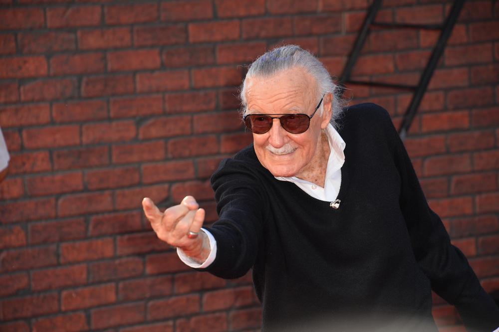 Stan Lee står och pekar framåt med ett finger. Han har grått hår som är bakåtkammat, mörka glasögon och en svart tröja.