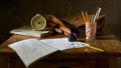 Foto på bok, pennor och skolbänk.