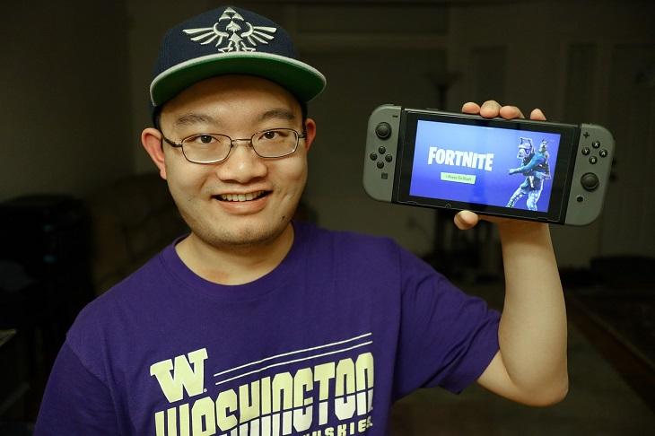 En person håller i en spelplatta och visar att hen spelar Fortnite. Hen har keps och glasögon.