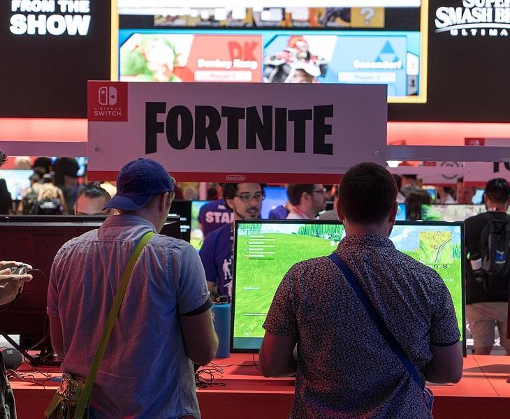 Två spelare står framför en dataskärm och spelar. Bortanför dem syns en skylt där det står Fortnite.