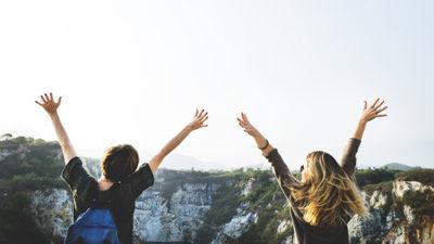 Foto på två tjejer som står med armarna uppsträckta vid en avsats.