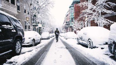 En väg som är täckt av snö. En människa går på vägen mellan några bilar.
