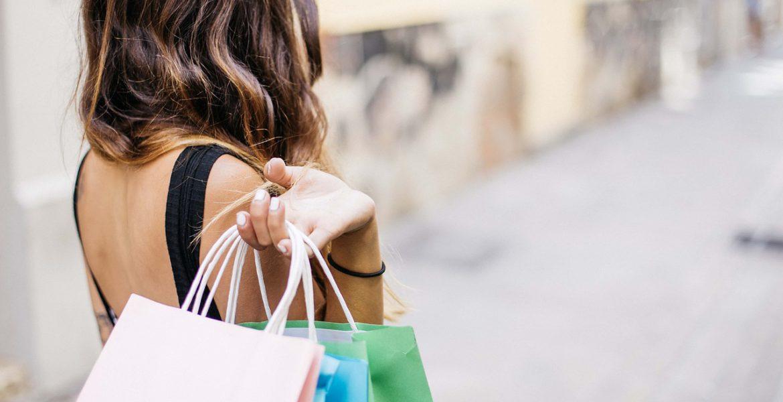 En person med långt hår går nerför en gata. Vi ser bara ryggen. Över axeln har hon slängt några shoppingpåsar.