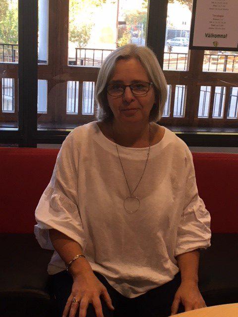 Annika sitter på en soffa. Hon har en stor tröja på sig. Hon har halvlångt grått hår och glasögon.