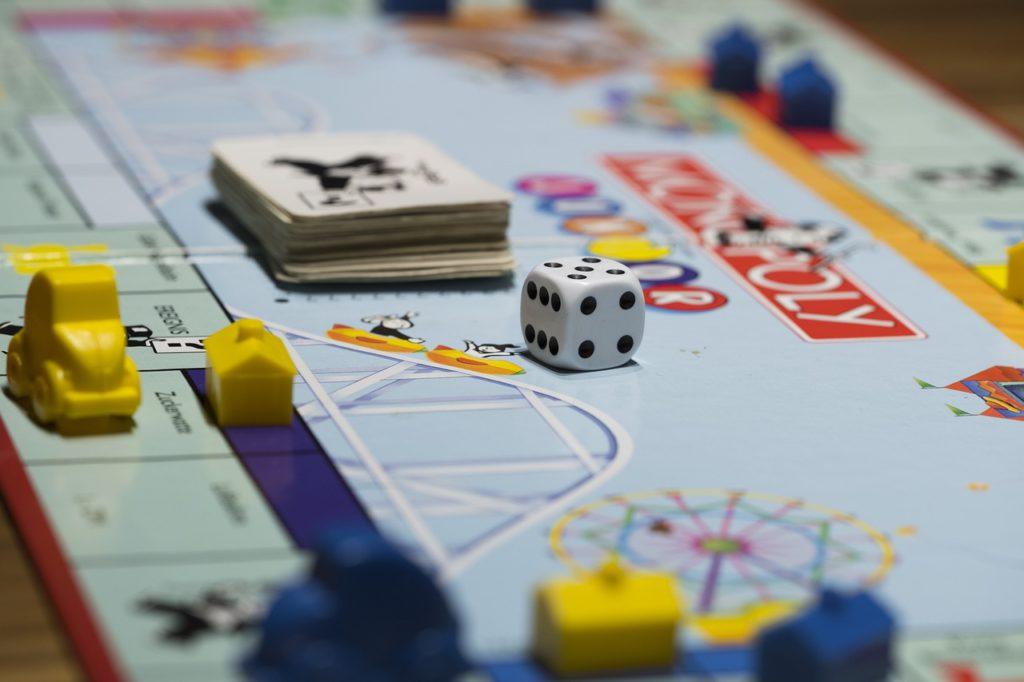 Monopolbräde med hus och kort och en tärning på.