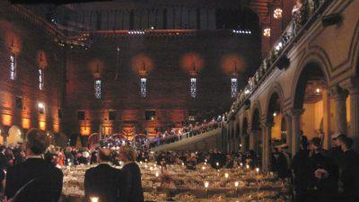 En bild på en stor sal med en stor trappa längst bort. I hela hallen är det fullt med långbord med fina dukar och porslin.
