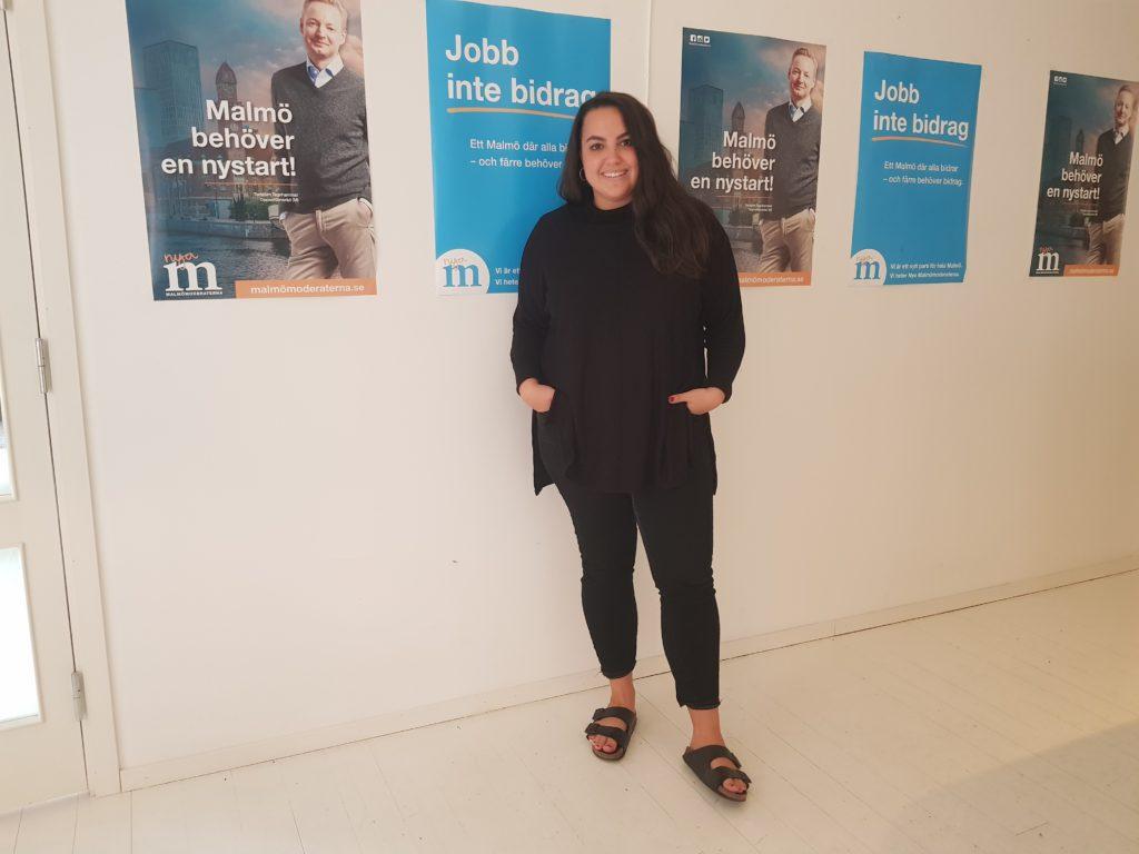 Noria på sitt kontor, framför affischer med Moderaternas logga och andra budskap.