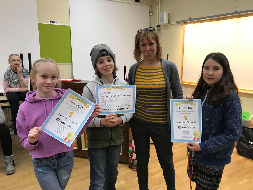 De fyra som syns på bilden står tillsammans i ett klassrum. De tre barnen håller i var sitt diplom och ser glada ut.