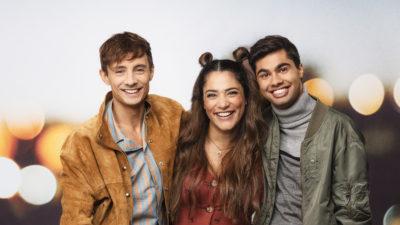De tre programledarna står och håller om varandra och skrattar.