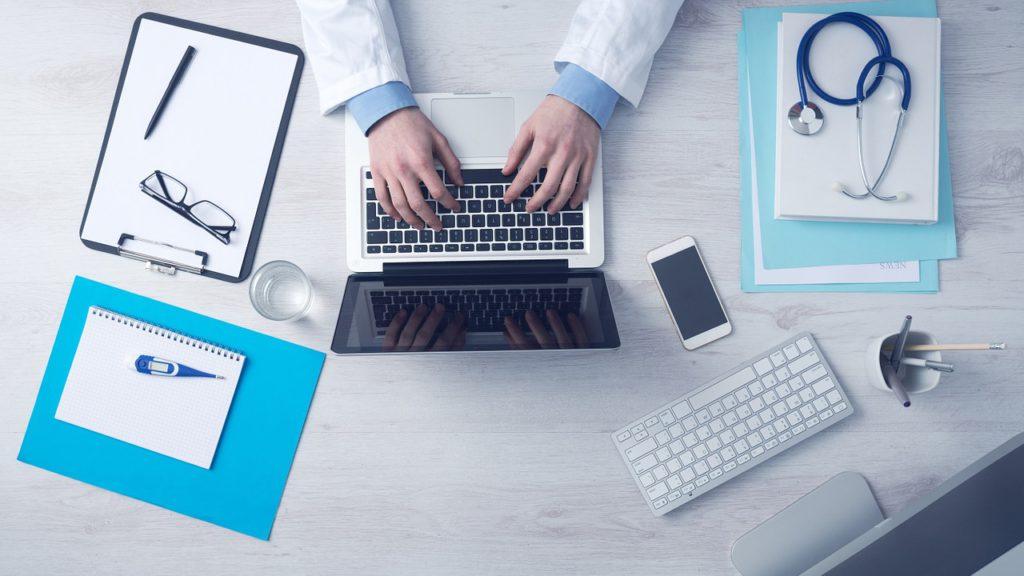 En dator uppifrån. På tangentbordet syns två händer som skriver. Runt datorn ligger typiska läkarsaker: ett stetoskop, en termometer och en skrivplatta.