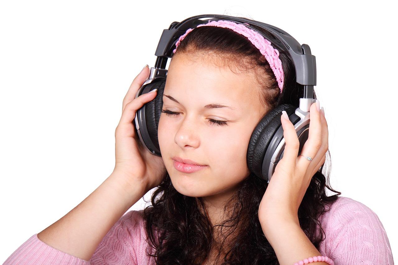 En person med långt hår har på sig stora hörlurar. Hon blundar och håller händerna på hörlurarna som att hon lever sig in i musiken som spelas.