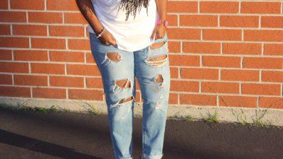 En person med hål på sina jeans står utomhus
