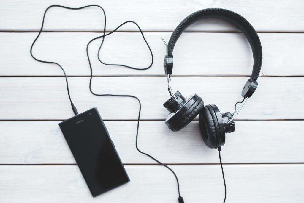 En mobil ligger på ett bord. Det är inkopplat ett par hörlurar till telefonen som ligger bredvid.
