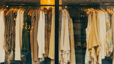 En rad med massa kläder som hänger i galgar