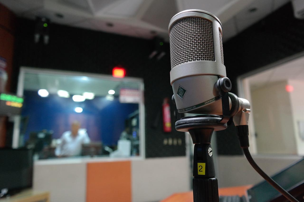 En mikrofon som sitter på ett stativ. I bakgrunden syns en studio.