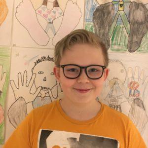 Elliot står framför en vägg med teckningar. Han har kort hår och glasögon. Han ser glad ut.