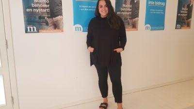 Noria står framför en vägg med affischer. Affischerna är reklam för moderaterna. Hon en långt tröja, thights och tofflor. Hon har långt vågigt hår och ler stort.