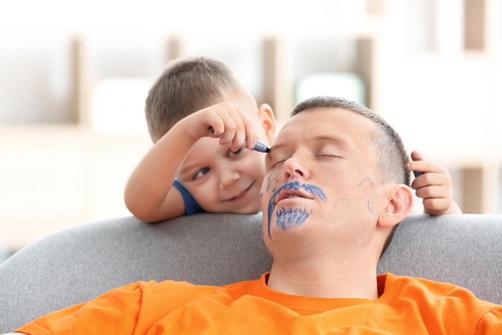 En person ligger och sover i en fåtölj. Två barn har smugit upp bakom personen och målar en mustasch och skägg utan att han märker något.