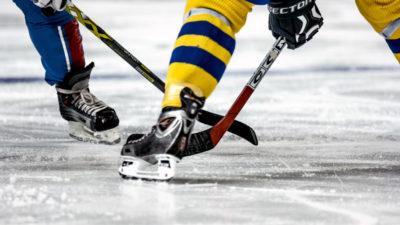 Två ishockeyspelare står på isen och tekar. Bara deras ben syns. Den ena har Sveriges färger på kläderna.