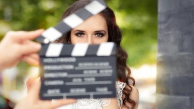En kvinna med långt lockigt hår. Framför henne håller två händer upp en svart tavla. Längst upp på tavlan är det en pinne som kan slås ihop för att markera när hon ska börja skådespela.