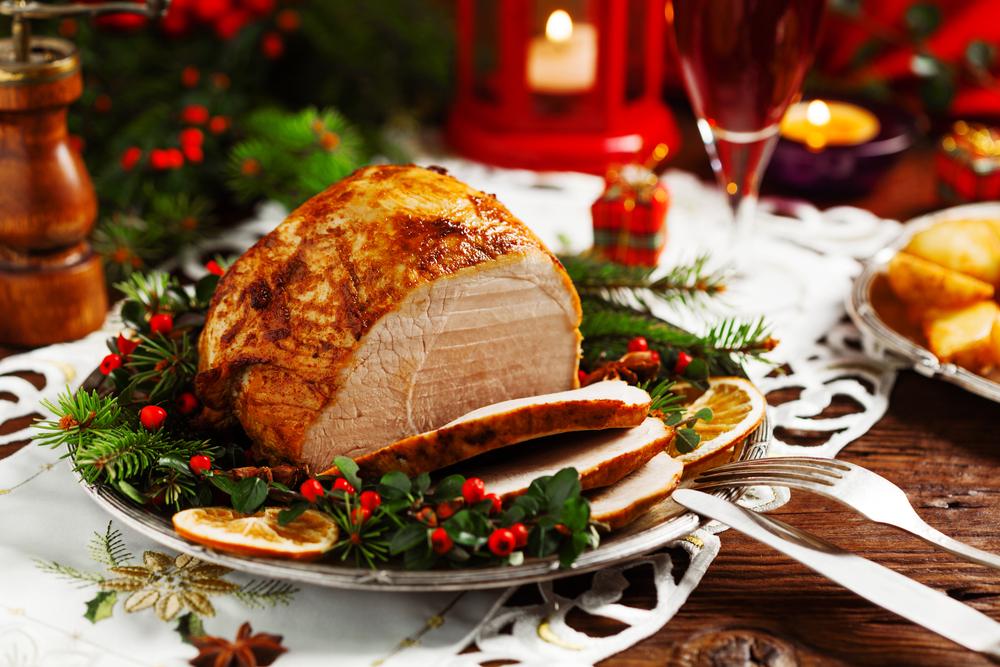 En julskinka ligger upplagd på en tallrik. Det är skuret några skivor av skinkan. På fatet runt skinkan är det grenar med bär och apelsinskivor.