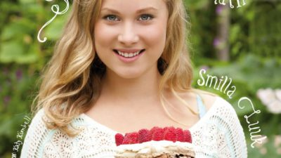 En bild på boken. Smilla står utomhus på sommaren. Hon ler och håller i en tårta som består av flera lager maräng med hela hallon och grädde emellan.