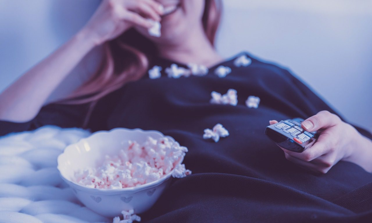 En tjej som äter popcorn. Hon håller i en fjärrkontroll.