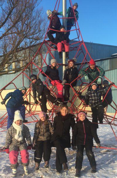 Läraren Petra sitter i skolgårdens klätterställning tillsammans med sina elever.