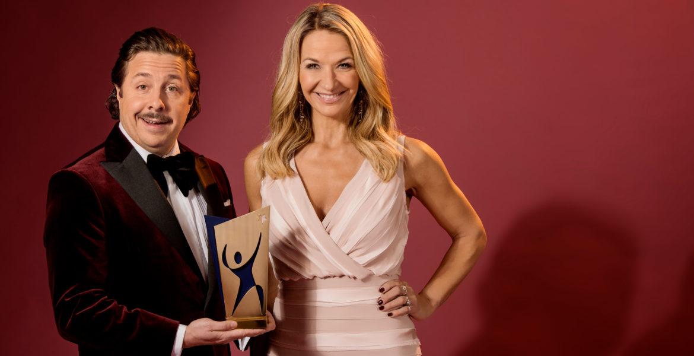 David och Kristin står i finkläder och ler stort. David håller i ett av galans priser. Priset är av metall och föreställer en siluett av en figur som höjer armarna.