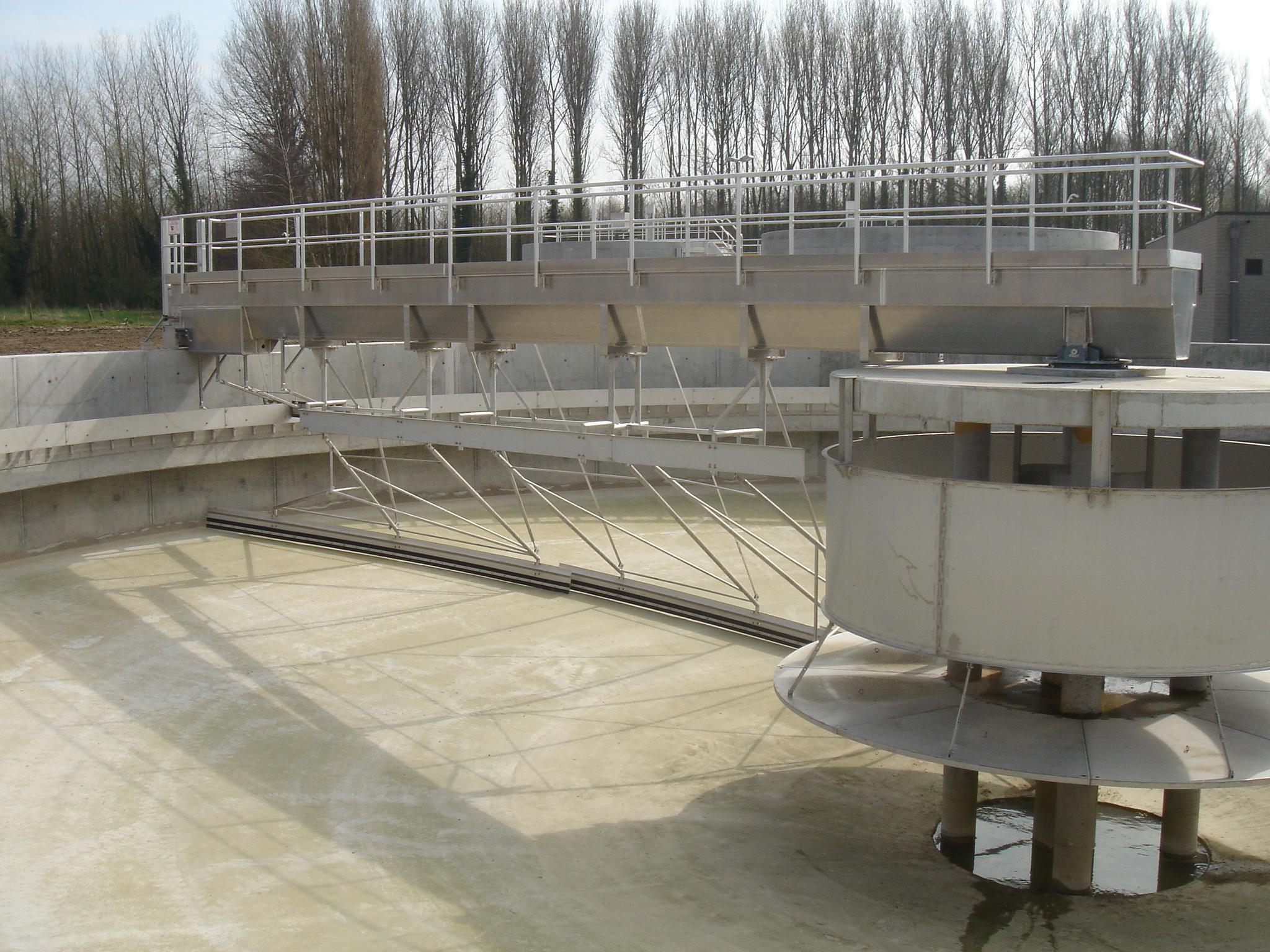 En stor maskin. I mitten är det en pelare med en lång arm på, som sträcker sig ut över en rund bassäng.