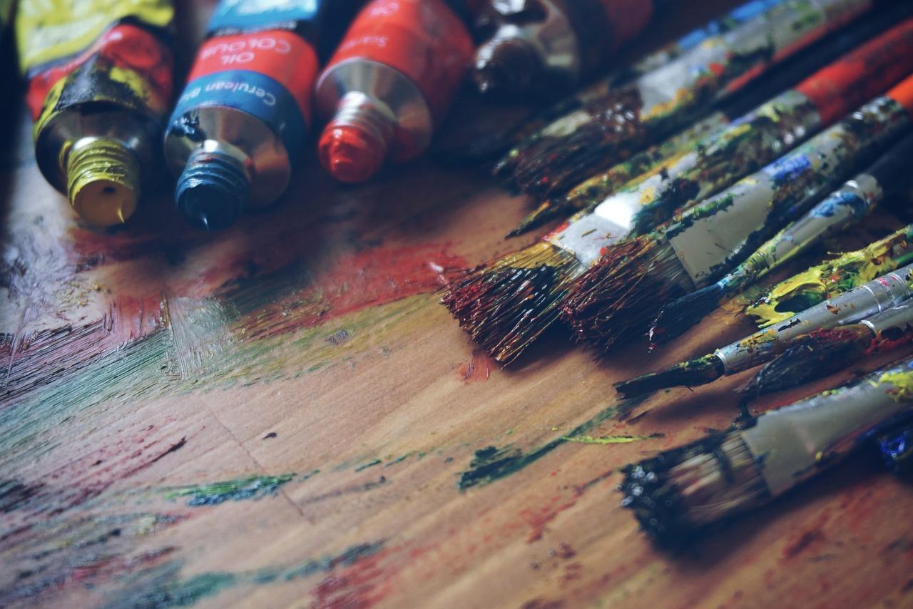 Många målarpenslar och färgtuber ligger på ett bord.