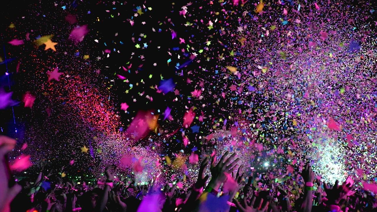 Massa konfetti sprutar ut över en folkmassa där människorna sträcker upp händerna i luften.