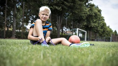 Julle sitter på en gräsmatta. Han knyter sina fotbollskor. Bredvid honom ligger en fotboll. I bakgrunden syns ett fotbollsmål.