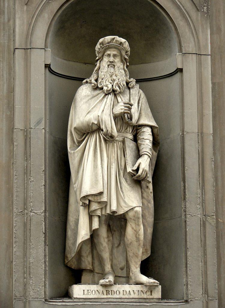 En vit stor staty. Den föreställer en man med toga och mantel och stort skägg.