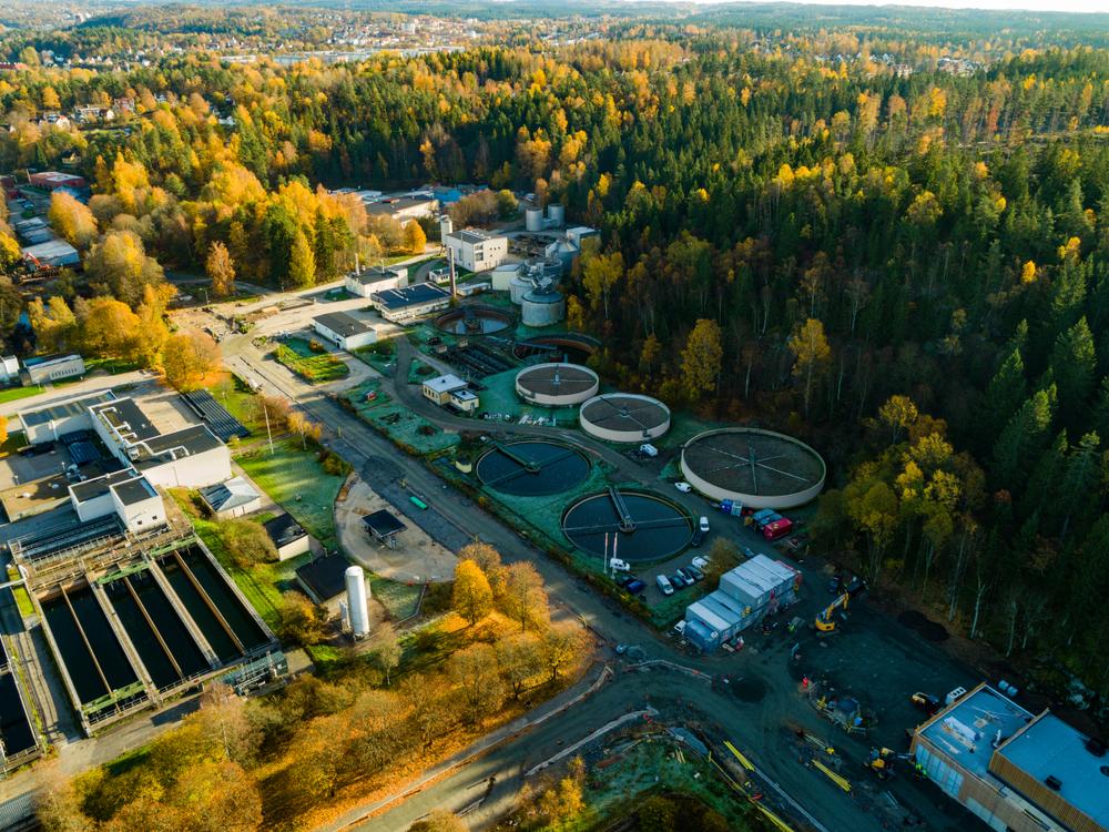 En bild uppifrån luften. Nedanför syns flera stora runda byggnader som ligger i utkanten av en skog. Runt byggnaderna finns också något som ser ut som stora bassänger.