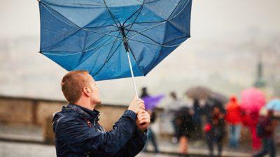 En person håller i ett paraply som håller på att blåsa iväg.