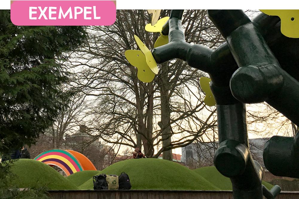 """En lekpark med gröna kullar och en skulptur. Mitt i bilden syns en väska på marken. Längst upp på bilden finns en ruta med texten """"Exempel""""."""