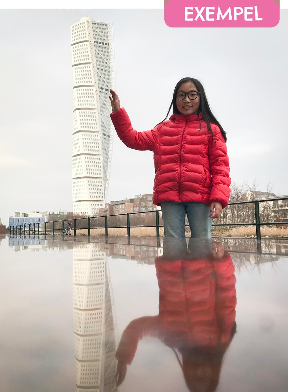 """Alma står framför det höga huset Turning Torso i Malmö. Hon håller upp handen så det ser ut som att hon tar på tornet. Ovanför henne är det en textruta där det står """"Exempel""""."""