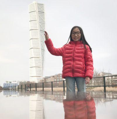 Alma håller sin hand mot byggnaden Turning torso. Alma är nära kameran, byggnaden är långt borta, ändå ser det ut som att Alma lutar handen mot höghuset.