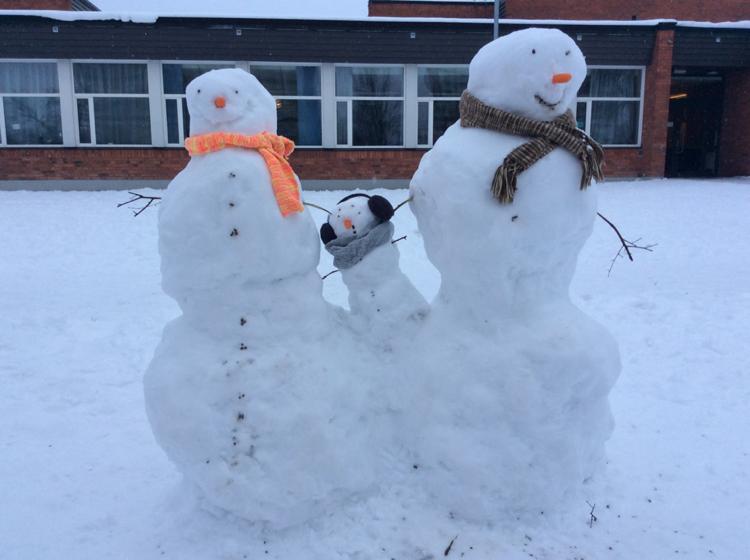 Tre snögubbar utanför en skola