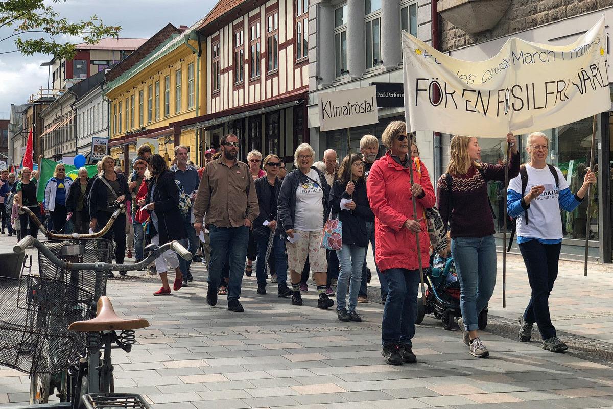 Många människor går genom en stad i ett demonstrationståg. Längst fram går några personer som håller i ett stort banér.