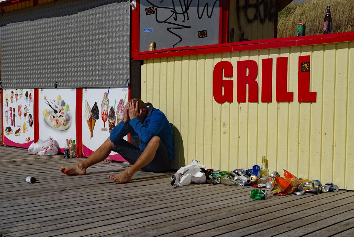 """En ensam person sitter utanför ett hus där det står """"grill"""". Personen håller händerna för ansiktet. Bredvid personen ligger det massa gamla ölburkar."""